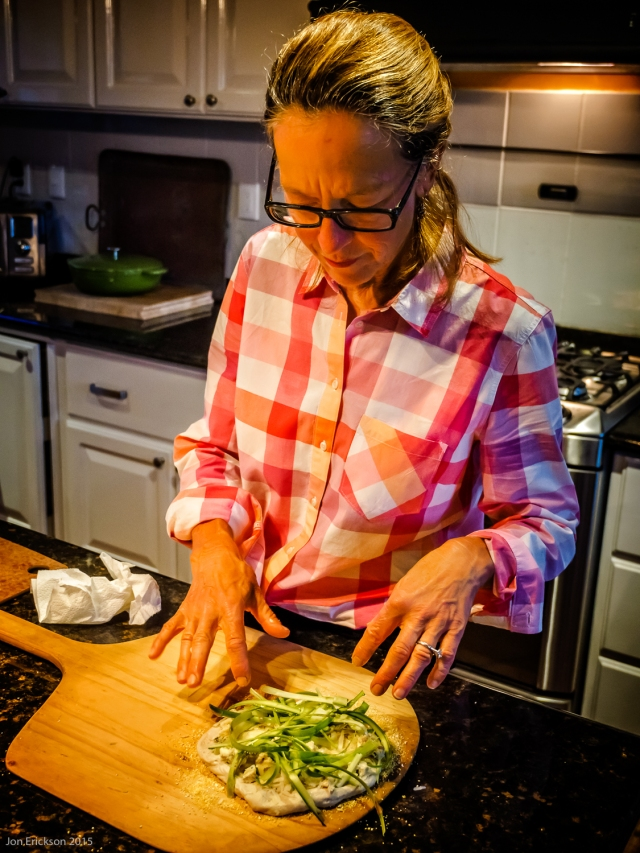 Jo Ann preparing the pizza by ensuring the asparagus is properly positioned.